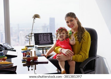 Busy businesswoman with little daughter in office. The executive mom spends time with her child and takes her at work - stock photo