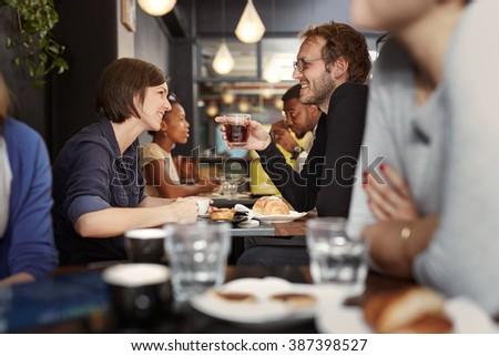 Busy cafe with a young couple smiling at each other - stock photo