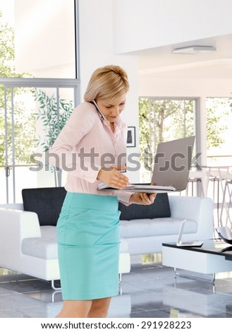 Busy casual caucasian blonde businesswoman working at home using mobile phone, folder in hand, standing, talking, elegant. - stock photo