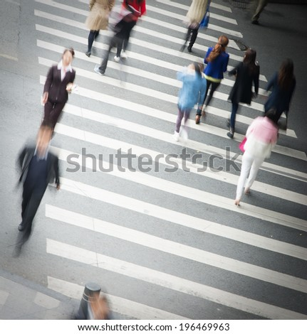 Busy city street people on zebra crossing - stock photo