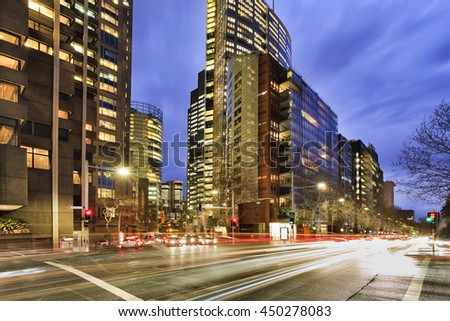 Busy city streets traffic in Sydney at intersection of Elizabeth street with illuminated office buildings at rush hour during sunset. - stock photo