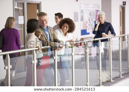 Busy College Corridor With Mature Students Talking - stock photo