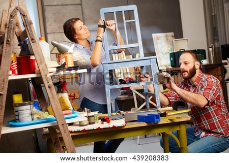 Busy couple renewing chair in home workshop. - stock photo