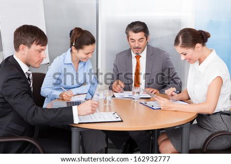 Busy Coworkers Working Together At Desk In Office - stock photo