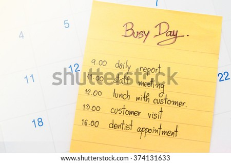 Busy day and plan in yellow stick note on calendar. - stock photo