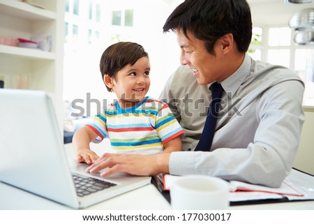 Busy Father Working From Home With Son - stock photo
