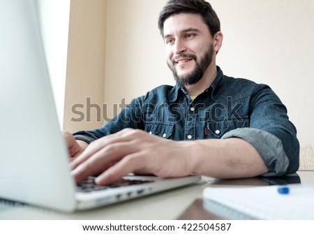 Busy handsome businessman in home office working on his laptop - stock photo