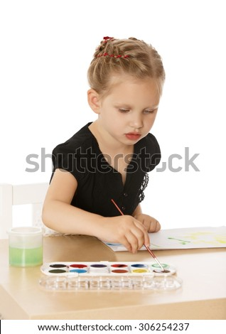 Busy little girl drawing at the table with watercolors. Girl brush smears of dried paint-Isolated on white background - stock photo