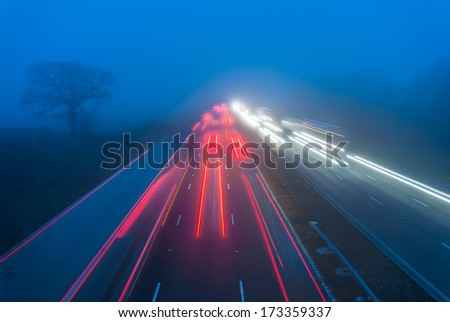 Busy M6 motorway traffic motion at night in fog creating abstract image. - stock photo