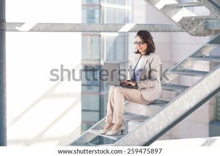Busy mid adult businesswoman sitting on the stairs using laptop. - stock photo