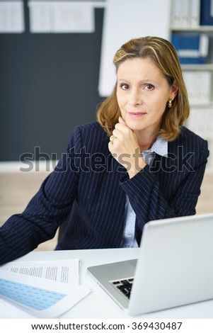 Busy middle-aged businesswoman with a distracted expression pausing while reading documents at her desk to look at the camera - stock photo
