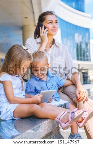 Busy mother with mobile phone, kids sit with electronic tablet - stock photo
