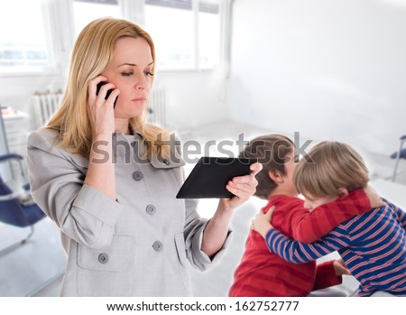 busy mother with tablet and mobile while her children fighting - stock photo
