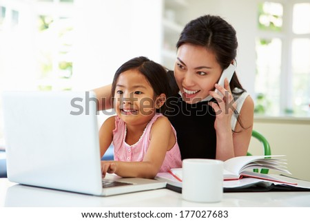 Busy Mother Working From Home With Daughter - stock photo