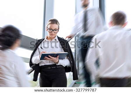 Busy office building corridor, three business people in a motion, focus on woman standing and taking notes - stock photo