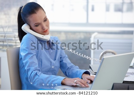 Busy office worker girl taking landline phone call while typing on laptop computer.? - stock photo