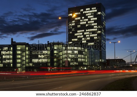 Busy road with office buildings in Munich, Germany, at night - stock photo