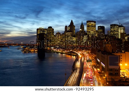 Busy traffic in New York City Manhattan with Brooklyn Bridge at dusk - stock photo