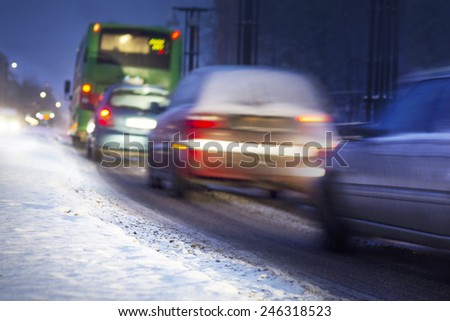 Busy traffic in snowy winter evening - stock photo