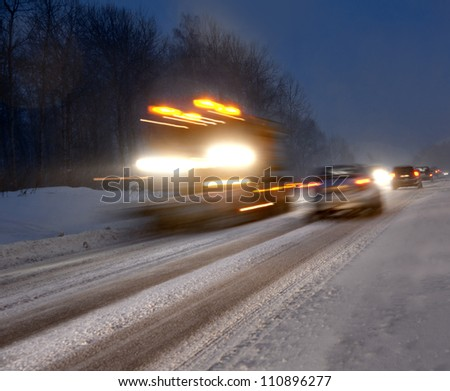 Busy traffic on country road at night in heavy snowstorm - stock photo