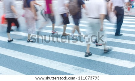 Busy urban street people on zebra crossing - stock photo