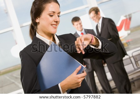 Busy woman is looking at her watch in an airport - stock photo