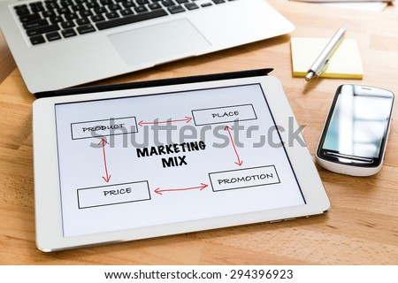 Busy working desk with tablet showing the information of marketing mix concept - stock photo