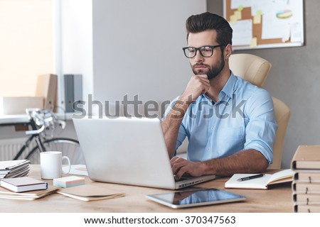 Busy working. Pensive young handsome man wearing glasses working on laptop and keeping hand on chin while sitting at his working place - stock photo