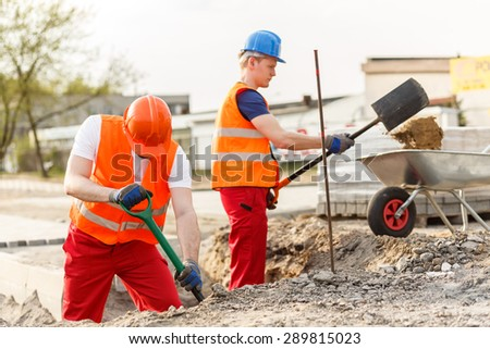Busy young builders digging on construction site - stock photo