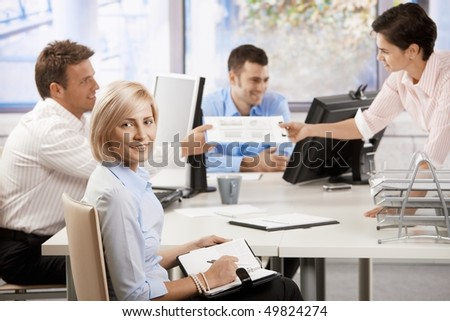 Busy young business people working in office at desk, smiling. - stock photo