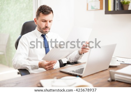 Busy young businessman with a beard reviewing some performance charts in his office - stock photo
