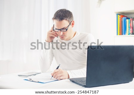 Busy young man talking on mobile phone while sitting in front of laptop looking at paperwork - stock photo