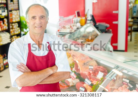 Butcher proud of his shop - stock photo