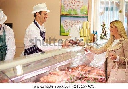Butcher Serving Customer In Shop - stock photo