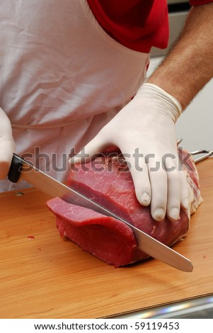 butcher slicing meat, cutting meat in the kitchen. - stock photo