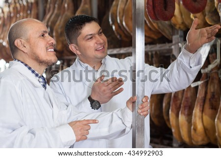 Butchery technologists in white gown checking joints of iberico jamon at factory - stock photo