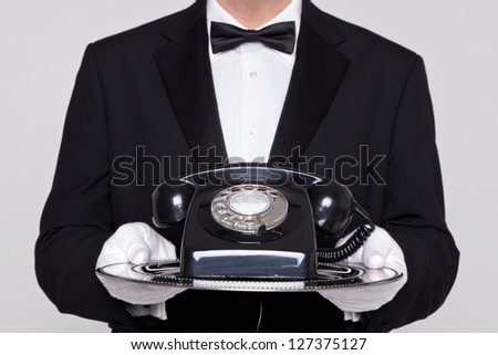Butler holding a silver tray with an old retro black telephone on it. - stock photo