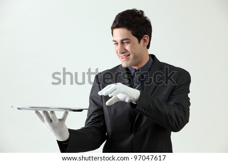 Butler holding an empty silver tray - stock photo