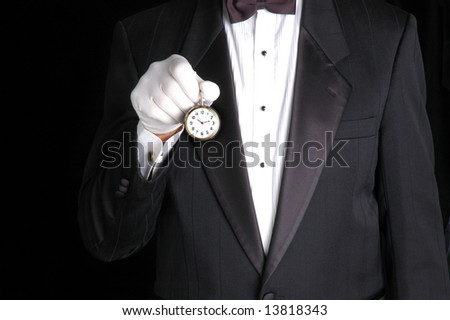 Butler in Tuxedo Holding a Pocket Watch with the Face pointing towards camera - stock photo