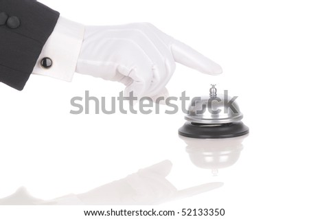 Butler's gloved hand extended over service bell isolated on white. Hand and arm only in horizontal format with reflections. - stock photo