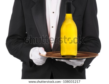 Butler wearing a tuxedo holding a bottle of Chardonnay Wine on a serving tray. Horizontal format showing persons torso only. - stock photo