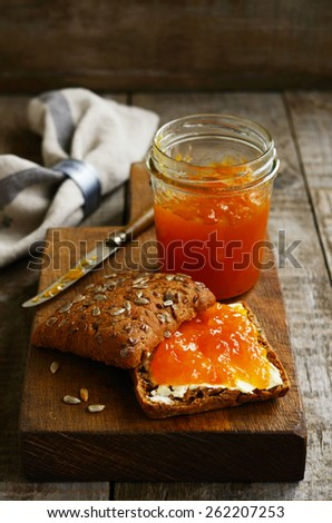 Butter and apricot jam rye sandwich with sunflower seeds on cutting board on rustic wooden background - stock photo