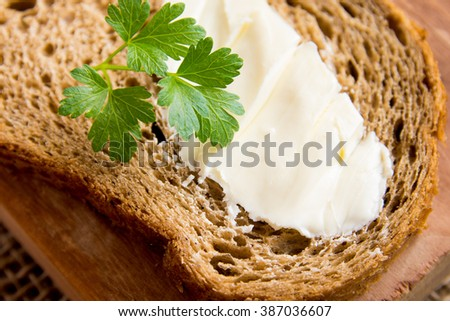 Butter and bread for breakfast, with parsley over rustic wooden background - stock photo