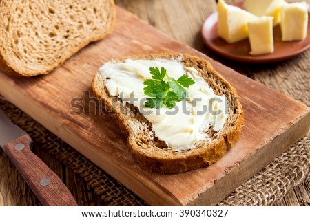 Butter and bread for breakfast, with parsley over rustic wooden background close up - stock photo
