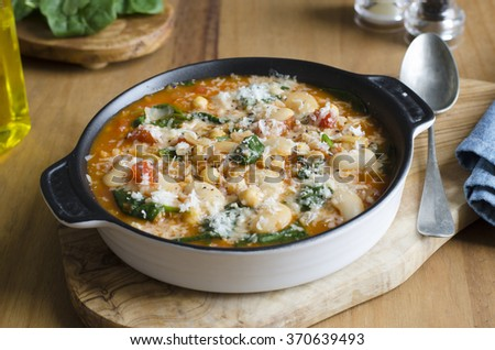 Butter bean, chickpea and spinach soup topped with grated Parmesan - stock photo
