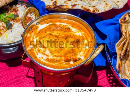 Butter Chicken halal indian food Photo of an Indian meal of Butter Chicken, rice and naan. Focus across the Butter Chicken bowl. - stock photo