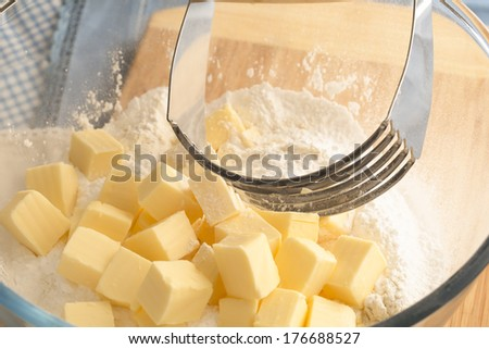 Butter in bowl with flour and handheld pastry blender. - stock photo
