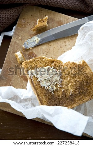 butter on bread toasted put on messy cutting board - stock photo