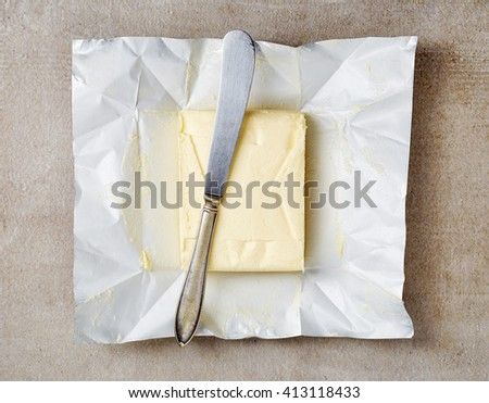 Butter package with knife, top view - stock photo