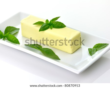 Butter stick on a white dish with basil leaves - stock photo